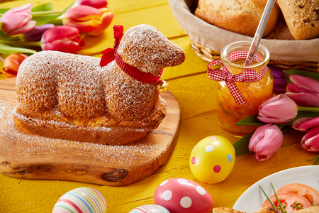 Gourmet lamb shaped Easter cake with colorful eggs and tulips on a festive table Archivio Fotografico