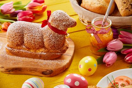 Pastel de Pascua en forma de cordero gourmet con coloridos huevos y tulipanes en una mesa festiva Foto de archivo - 96339391