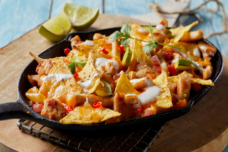 Spicy Mexican chicken with nachos and fresh herbs drizzled with cream and served in a rustic skillet in a close up view