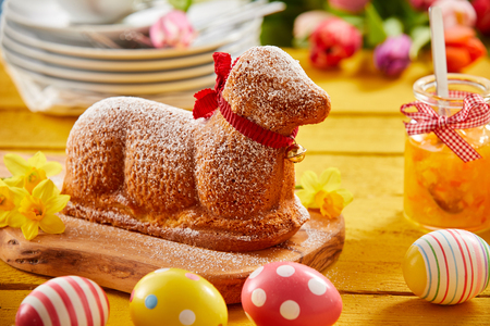 Cute speciality Easter cake in the shape of a lamb with a festive red bow around its neck on a table with colourful decorated eggs and fresh spring flowers
