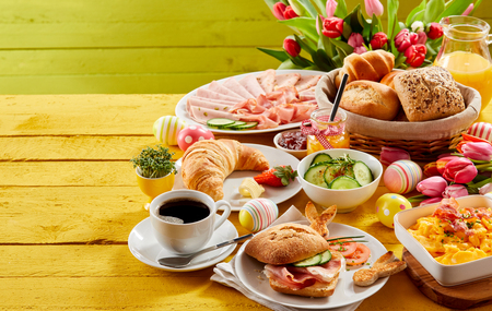 Easter buffet breakfast or brunch with assorted bread rolls, cheese, meat, scrambled egg, orange juice, coffee on a wooden table decorated with easter eggs and spring flowers with copy space Stockfoto