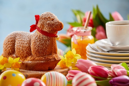 Speciality Spring Lamb cake on an Easter table decorated with colorful eggs, fresh tulips and daffodils and a stack of plates with a cup of coffee