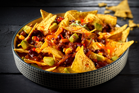 Delicious speciality chili con carne with nachos and melted cheese topped with fresh avocado and coriander in a close up view