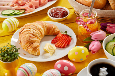 Delicious Easter breakfast on a decorated table with colorful eggs and a freshly baked croissant and strawberry served with jam, cold meats, cheese and coffee Standard-Bild