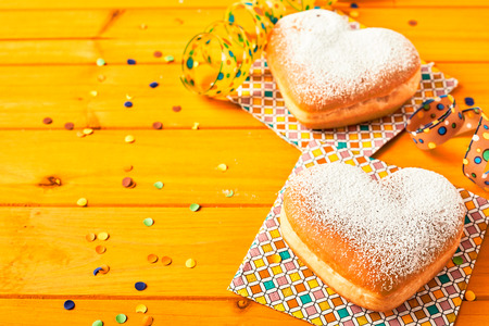 Couple of romantic heart shaped donuts on colorful paper napkins over a yellow wood table with scattered confetti and copy space