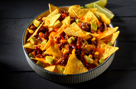 Chili con carne with Mexican tortillas or nachos and cheese topped with diced fresh avocado baked in the oven and served with lemon over a dark background in a close up high angle view Stock Photo