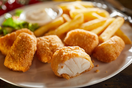 Tasty seafood appetiser of fried kibbeling, a Dutch recipe of bite size portions of breaded cod served with potato chips and salad 版權商用圖片