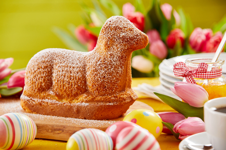 Freshly baked Spring lamb shaped Easter cake on a festive table with colorful eggs and fresh tulips