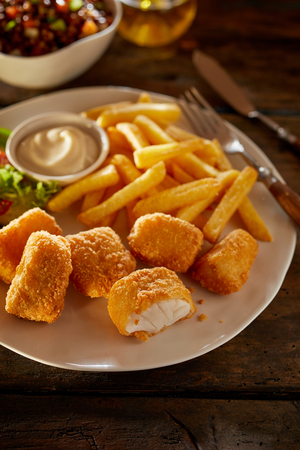 Tasty seafood snack or appetizer of fried kibbeling or bite sized portions of breaded codfish served with potato chips, salad and a mayonnaise dip Stockfoto