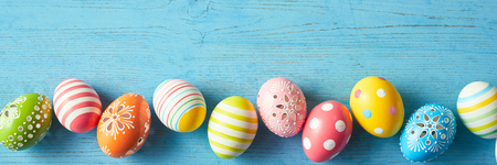 Panorama banner with a border of colorful decorated Easter eggs with stripes, polka dots and flowers on a blue wood background with copy space