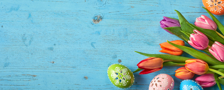 Tulip flowers and painted Easter Eggs on blue wooden background with copy space. Stock Photo