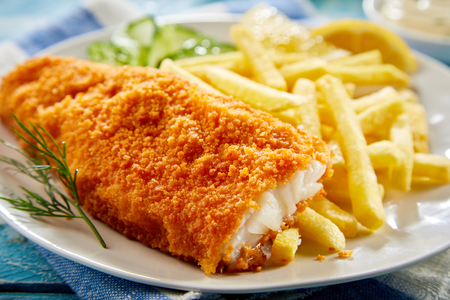Het gedeelte van knapperig gepaneerd visfilet met frieten diende op plaat