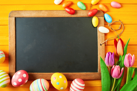 Old blank vintage slate with copy space framed by colorful Easter eggs and fresh spring tulips on a yellow wood background