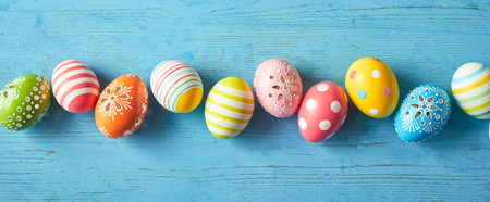Row of colorfully painted Easter eggs on blue wooden background, wide angled image.