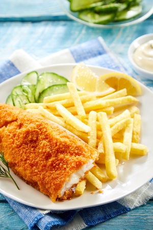 Crispy deep fried fillet of codfish with breadcrumbs served with French fries and a fresh cucumber salad 版權商用圖片