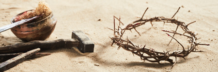 Religious Easter banner conceptual of the crucifixion with a crown of thorns, old iron nails, hammer and bowl with bloody sponge and spear on sand