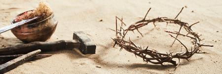 Religiöse Ostern-Fahne begrifflich von der Kreuzigung mit Dornenkrone, alten Eisennägeln, Hammer und Schüssel mit blutigem Schwamm und Stange auf Sand