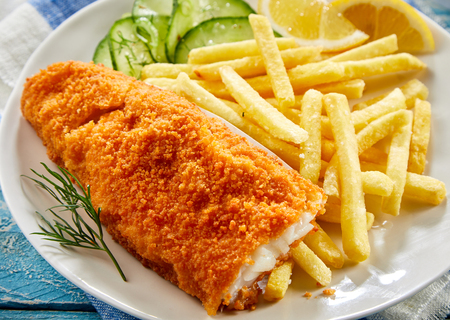 Portion of crispy fish with french fries served on plate