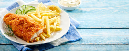 Crumbed deep fried fillet of cod served with potato chips and a cucumber salad on rustic blue wood in panorama banner format with copy space