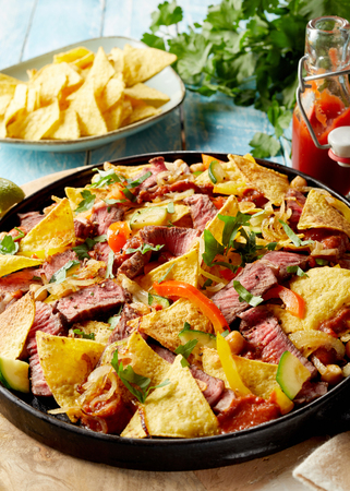 Speciality Tex-Mex recipe with beef entrecote, nachos, spicy chili peppers, coriander and cheese in a shallow dish served with tomato ketchup