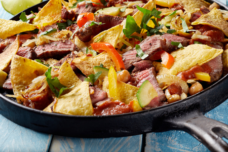 Thinly sliced tender medium rare roast beef entrecote steak with nachos au gratin, chili peppers and fresh coriander in an old skillet in a close up view