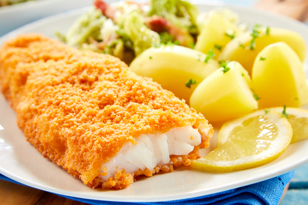 Close up view of crispy breaded fish served on plate with potatoes