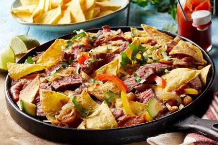 Spicy Tex-Mex beef entrecote steak with nachos oven baked with cheese served in an old cast iron skillet garnished with fresh coriander 版權商用圖片
