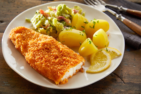 Crispy golden crumbed codfish fillet served with boiled baby potatoes and salad on a rustic wooden table