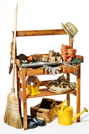 Rustic wooden shelves with garden supplies including flowerpots, potting soil, watering can, nesting box, shoes, sunhat and twine over a white background Imagens