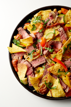 Dish of tender spicy beef entrecote with nachos, chili peppers and fresh coriander in an overhead view on white