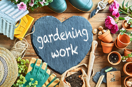 Slate heart with handwritten text - Gardening Work - surrounded by assorted garden supplies and tools, a nesting box, sunhat, shoes and summer flowers in an overhead view