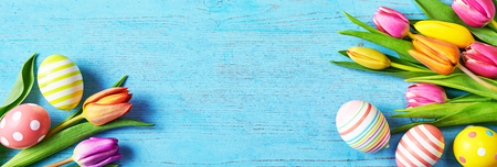 Pretty turquoise blue Easter banner with colorful fresh spring tulips and scattered patterned Easter eggs and copy space for a holiday greeting or header