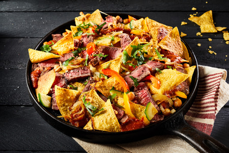 Hot spicy Mexican beef entrecote with nachos, chili peppers and fresh coriander served in an old vintage skillet on a striped kitchen cloth Stockfoto