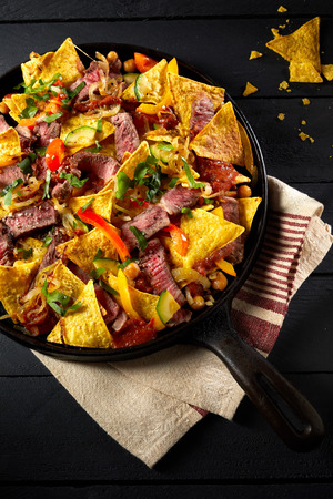 Spicy beef entrecote steak, chilis and nachos topped with cheese and seasoned with fresh coriander in an old iron skillet viewed from above