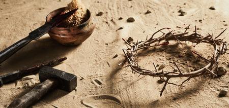 Corona naturale di spine con spugna sanguinante, lancia, vecchi chiodi di ferro e un martello sdraiato sulla sabbia simbolica della crocifissione di Cristo e Pasqua Archivio Fotografico - 97063088