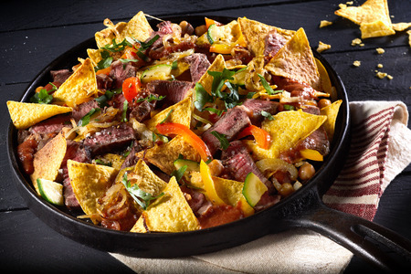 Tender spicy beef entrecote steak with red hot chili peppers, nachos and a topping of cheese and fresh coriander served in an old iron skillet in a high angle view