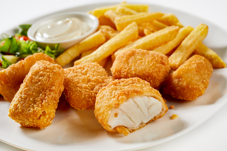 Tasty seafood appetizer of breaded kibbeling, a Dutch recipe for bite sized deep fried portions of codfish served with potato chips and mayonnaise
