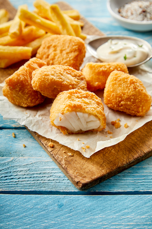 Tasty snack of fried breaded kibbeling, or bite sized portions of codfish, served on paper on a wooden board with a side dish of mayonnaise 版權商用圖片