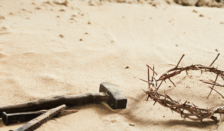Religious Easter background with crown of thorns, a large old iron nail and small hammer on sand with copy space Stock Photo