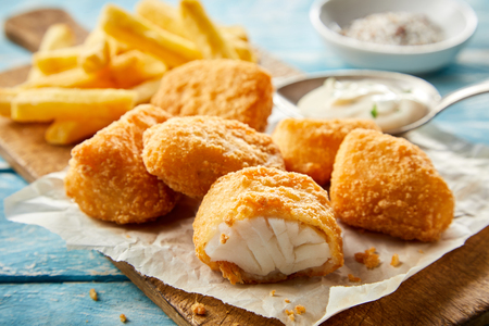 Regional Dutch cuisine with breaded kibbeling or small portions of deep fried codfish in a close up view on a wooden board sliced through to show the fish Reklamní fotografie