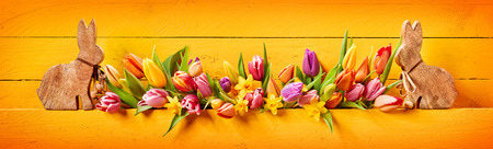 Pretty colorful Easter panorama banner with fresh spring flowers and two cute little wooden bunnies at either end over a brightly colored yellow wood background with vignette