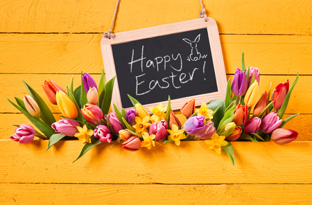 Happy Easter message handwritten on a vintage school slate with fresh spring tulips and daffodils on a colorful yellow wood background with copy space Archivio Fotografico