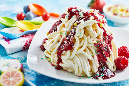 Close up view of spaghetti ice cream dessert with raspberry fruit sauce Banco de Imagens