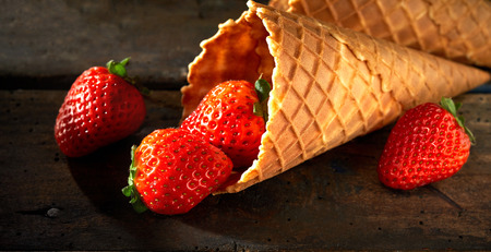 Tasty fresh ripe red strawberries in a cornet or waffle ice cream cone spilling onto a rustic wood counter in banner format