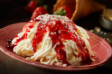 Bowl of ice cream noodles or ramen with berry syrup or coulis in a close up side view