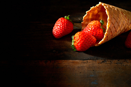 Fresh summer strawberries in an ice cream cone or cornet arranged in the corner spilling onto a dark rustic wood table with copy space Foto de archivo - 97595399