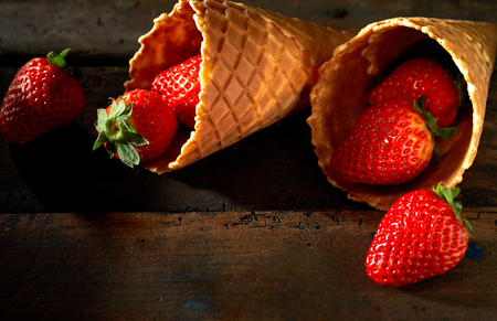 Fresh ripe red strawberries in ice cream cones spilling out onto a rustic wood surface with copy space
