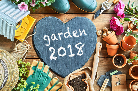 Garden season 2018 concept overhead photo of gardening equipment arranged on the floor, with grey heart-shaped board with white inscription 스톡 콘텐츠