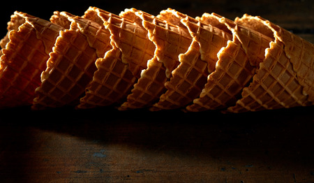 Stacked empty cornets or ice cream waffle cones on shadowy dark rustic wood with highlights for texture and copy space Foto de archivo - 97595403