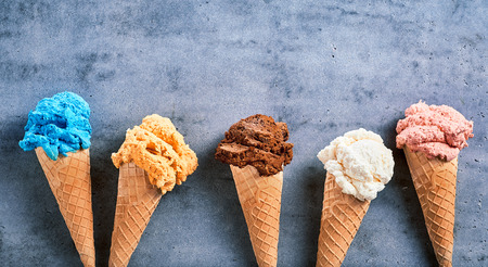Assorted speciality ice cream flavors in sugar cones in banner format arranged as a border with copy space on textured slate with copy space